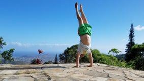 Homem Handstanding na montanha superior fotografia de stock