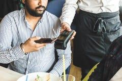 Homem hindu atrativo novo que paga no café com pagamento sem contato do smartphone fotos de stock royalty free