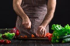 Homem home novo do cozinheiro no avental que corta a cenoura com faca de cozinha Imagens de Stock