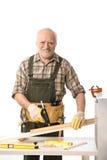 Homem idoso alegre que conserta Foto de Stock