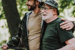 Homem idoso alegre que descansa com seu filho adulto imagem de stock royalty free