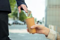 Homem idoso bem sucedido que põe o dinheiro no copo para sem abrigo fotografia de stock royalty free