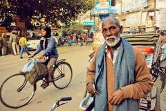 Homem idoso com a barba branca que está com a bicicleta na rua movimentada da cidade índia de Varanasi imagens de stock