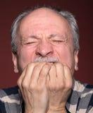 Homem idoso com a cara fechado pelas mãos Imagens de Stock