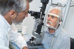 Homem idoso com glaucoma no ótico para o exame ótico fotografia de stock