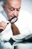 Homem idoso com magnifier fotos de stock