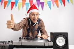 Homem idoso com o chapéu do Natal que faz o polegar acima do sinal Imagens de Stock Royalty Free