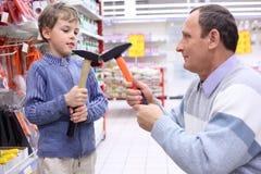 Homem idoso com o menino na loja com martelos Foto de Stock