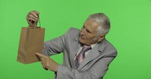 Homem idoso com saco de compras Olha na câmera e estica o presente vídeos de arquivo
