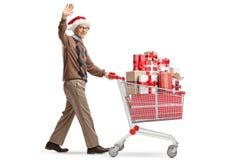 Homem idoso com um chapéu de Papai Noel que empurra um carrinho de compras com presentes e que acena na câmera imagem de stock royalty free