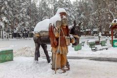 Homem idoso da vila da escultura de madeira com asno foto de stock