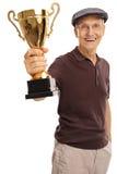 Homem idoso deleitado que guarda um troféu dourado imagens de stock