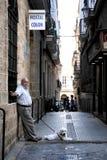 Homem idoso desconhecido com um cão em uma rua estreita da cidade antiga de Cadiz Imagem de Stock