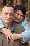Homem idoso do abraço da mulher adulta Fotografia de Stock