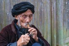 Homem idoso do chinease que ilumina uma tubulação Fotografia de Stock Royalty Free