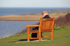 Homem idoso do pensionista no banco litoral foto de stock royalty free