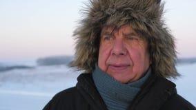 Homem idoso do retrato com os enrugamentos no revestimento e no chapéu forrado a pele exteriores no inverno vídeos de arquivo