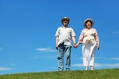 Homem idoso e mulher nos chapéus de palha que estão no monte foto de stock