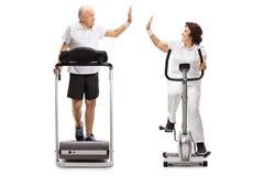 Homem idoso e uma mulher idosa que exercita e alta-fiving cada um Imagens de Stock Royalty Free