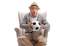 Homem idoso entusiasmado que guarda um futebol e que senta-se em uma poltrona imagem de stock