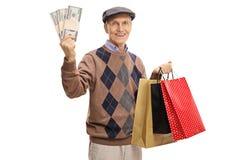 Homem idoso feliz que guarda pacotes e sacos de compras do dinheiro fotos de stock royalty free