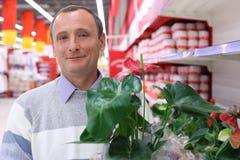 Homem idoso na loja com planta Imagens de Stock Royalty Free