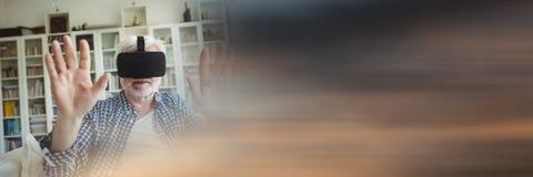 Homem idoso no sofá em auriculares da realidade virtual e na transição obscura do por do sol Fotografia de Stock
