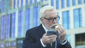 Homem idoso no terno que come o hamburguer que verifica o e-mail, trabalho fatigante, falta de tempo filme
