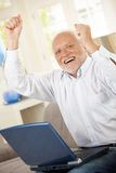 Homem idoso que comemora com portátil