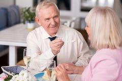 Homem idoso que dá a sua senhora um bolo imagem de stock royalty free