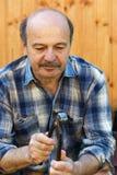 Homem idoso que guarda pares de alicates em sua mão Foto de Stock