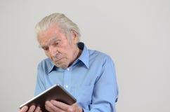 Homem idoso que guarda um PC moderno da tabuleta fotografia de stock