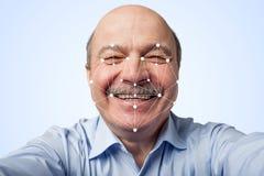 Homem idoso que guarda um smartphone que passa com o reconhecimento facial foto de stock royalty free