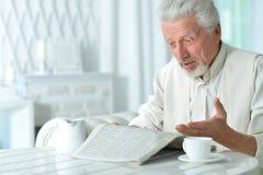 Homem idoso que lê um jornal imagens de stock