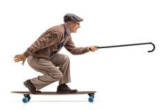Homem idoso que monta um longboard e que guarda um bastão imagens de stock royalty free