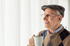 Homem idoso que olha através de uma janela imagem de stock