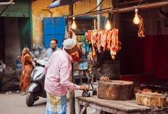 Homem idoso que olha na tenda do mercado de carne da rua velha da cidade índia imagens de stock royalty free