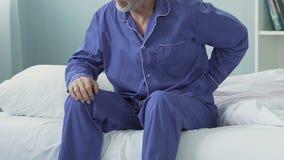 Homem idoso que senta-se na borda da cama, esticando e tendo a mais baixa dor nas costas repentina video estoque