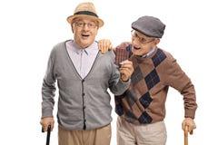 Homem idoso que sneaking acima em um outro homem idoso para agarrar uma mordida de foto de stock royalty free