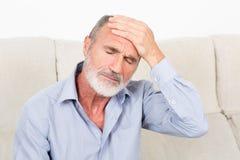 Homem idoso que sofre da dor de cabeça fotografia de stock royalty free