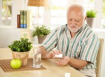 Homem idoso que toma o comprimido em casa Fotos de Stock Royalty Free