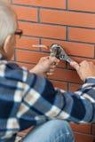 Homem idoso torneira chave parafusada Imagem de Stock