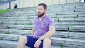 Homem impaciente novo que senta-se nas escadas que esperam alguém, tiro do slider filme