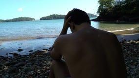 Homem incomodado pelo mar O homem novo que senta-se na praia, olhando preocupou-se Agarra sua cabeça video estoque