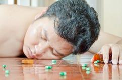 Homem inconsciente com comprimido disponível Imagens de Stock