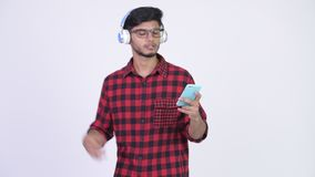 Homem indiano farpado feliz novo do moderno que escuta a música ao usar o telefone vídeos de arquivo