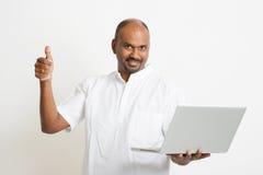 Homem indiano maduro que usa o portátil e o polegar acima imagens de stock royalty free