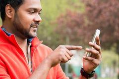 Homem indiano novo que usa o telefone celular com tecnologia do toque Imagem de Stock Royalty Free