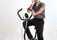 Homem indiano que exercita e que fala no telefone Fotografia de Stock Royalty Free