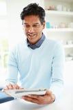 Homem indiano que usa a tabuleta de Digitas em casa Foto de Stock Royalty Free